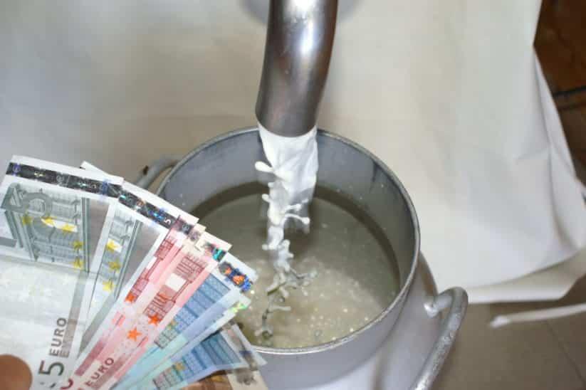 Milch fließt in eine Kanne; Geldscheine